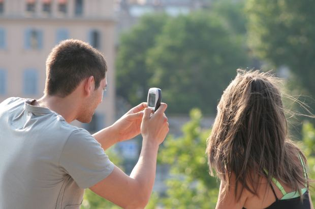 Boyfriend Taking Mobile Photo of Girlfriend