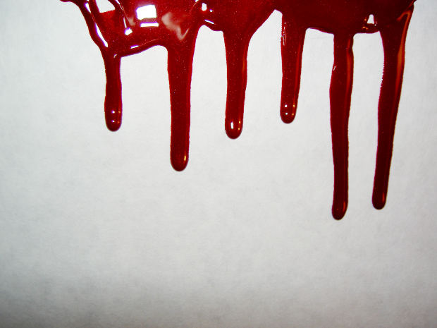 Red color blood dripping on the white wall